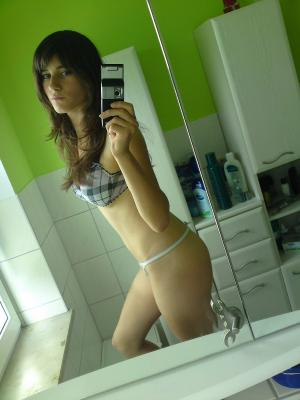 Nude girl makes selfies in front of the mirror